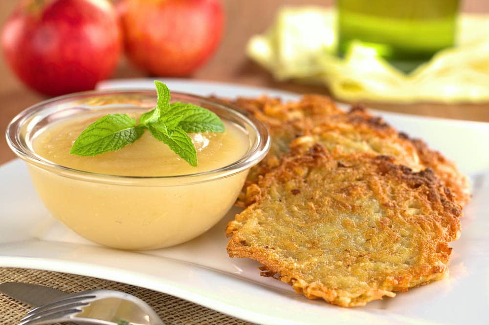 potato latkes and honey apple sauce on a white plate surrounded by ingredients to make them