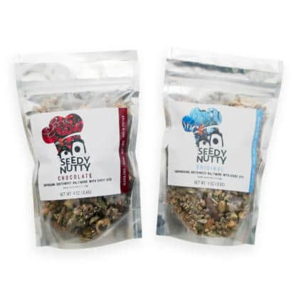 Two bags of Seedy Nutty granola mix on white background.