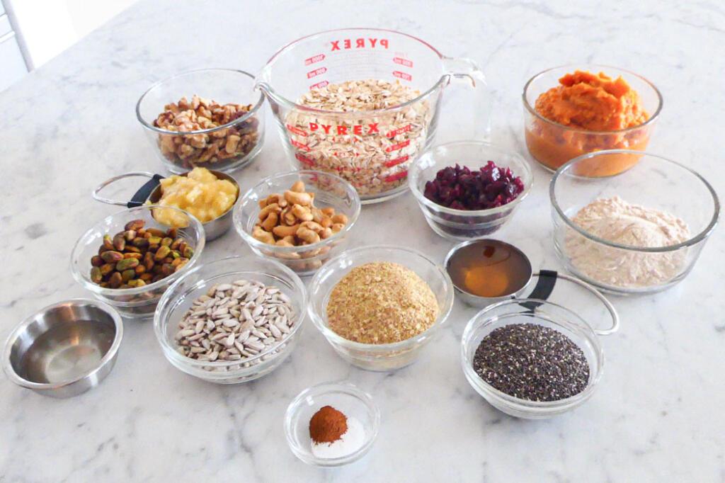 Ingredients to make nut and seed bread on marble countertop